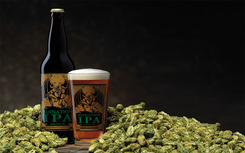 Stone ruination bottle and glass in a mountain of hops