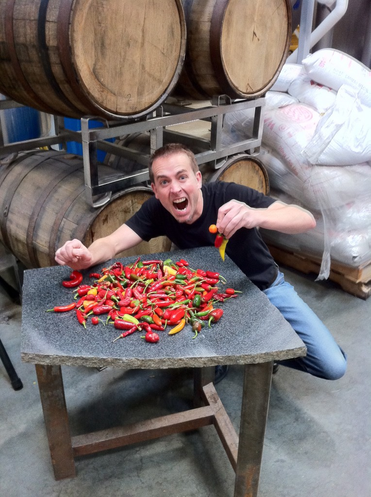 Greg holding chili peppers in front of a pile of chili peppers
