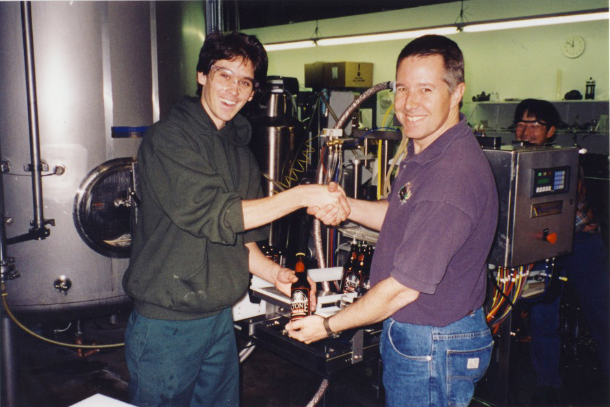 "Lee Chase and Steve Wagner showcasing our first ever 12 oz. bottle with Stone Brewer, Toshi Ishii looking on. Note that the ""Maheen"" bottling machine in the background is roughly the size of the three of them."
