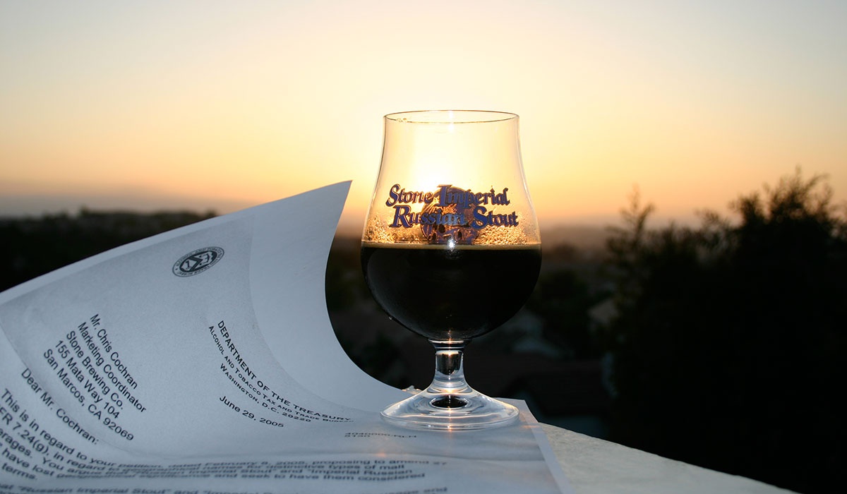 Glass of Stone Imperial Russian Stout in front of a sunset