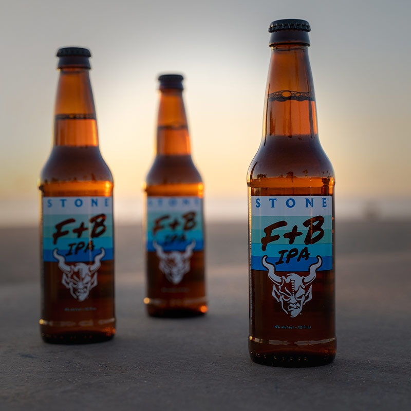bottles of Stone Features & Benefits Craft Light IPA on the beach.